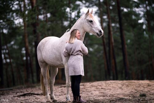 Mädchen kuschelt mit weißem Pferd auf Lichtung im Wald