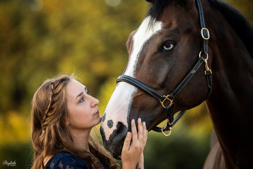 Blondes Mädchen und braunes Pferd mit Blesse und Halfter