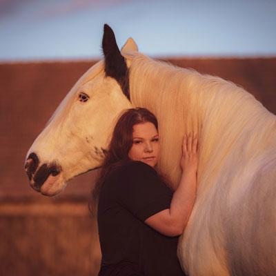 Frau kuschelt mit weißem Pferd