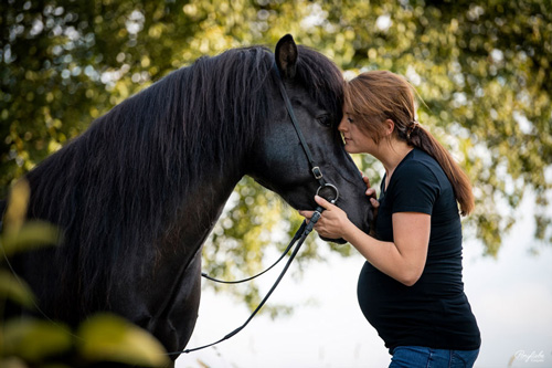 Schwangere Frau mit schwarzem Islandpferde kuscheln
