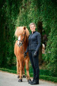 Hofportrait Ponyliebe Isländer Fuchs mit Trense und Frau in schwarzer Top Reiter Kleidung