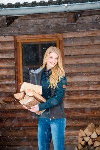 Krämer Pferdesport Katalogbilder Junge Frau vor Holzhütte mit Holz in der Hand und Schnee