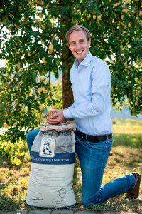 Mitarbeiter Portrait Ponyliebe lächelnder Mann im blauen Hemd und Jeans mit Futtersack und Futter in der Hand