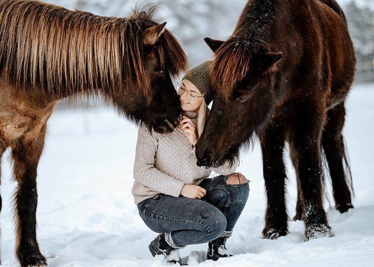 Pferdefotografin Ann-Christin Vogler von Ponyliebe Fotografie zwischen zwei Islandpferden im Schnee